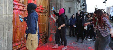 Mujeres pintan fachada y puerta de Palacio Nacional por feminicidio en México