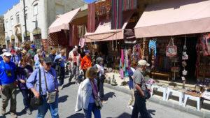 Bus-loads of visitors pack Madaba's souvenir shops.