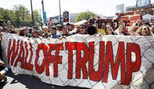 """Unos manifestantes Sostienen una pancarta en contra del magnate Donald Trump durante una manifestación llamada """"Wall Off Trump"""" (Amurrallar a Trump) realizada en la plaza Pública de Cleveland en Ohio. El intento de incendiar una bandera y el arresto de media docena de manifestantes fueron hoy los incidentes más destacados en las protestas de la Convención Republicana en Cleveland, donde las pasiones encontradas que levanta el candidato Donald Trump no pasan de provocaciones. EFE"""