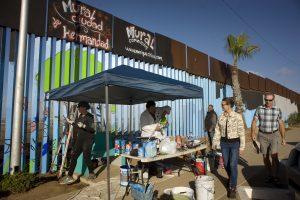 Turistas observan a los voluntarios que ayudan en la elaboración de murales en la cerca que marca el límite en la frontera entre EE.UU. y México hoy, jueves 1 de diciembre de 2016, durante el primer día de la realización de este proyecto en Tijuana (México). Un grupo de artistas inició hoy un proyecto sin precedentes bajo el cual cientos de voluntarios de distintas partes del mundo se unirán para ponerle color a más de dos mil metros lineales del muro fronterizo entre México y Estados Unidos. EFE