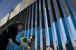 Victoria Dowding (i) and Getsemani Bustillos ayudan en la elaboración de murales en la cerca que marca el límite en la frontera entre EE.UU. y México hoy, jueves 1 de diciembre de 2016, durante el primer día de la realización de este proyecto en Tijuana (México). Un grupo de artistas inició hoy un proyecto sin precedentes bajo el cual cientos de voluntarios de distintas partes del mundo se unirán para ponerle color a más de dos mil metros lineales del muro fronterizo entre México y Estados Unidos. EFE